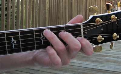 This is the wrong way to place your fingers on the guitar frets.